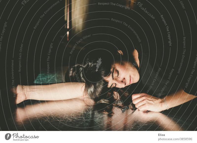 Portrait einer am Boden liegend schlafenden Frau mit geschlossenen Augen im Sonnenlicht geschlossene Augen entspannt genießen Spiegelung feminin Junge Frau