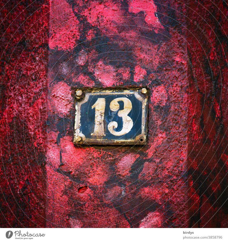 Verwitterte Hausnummer 13 auf rot - schwarzer Hauswand. Zahl 13 verwittert alt Rost Farbe Aberglaube Ziffern & Zahlen Zentralperspektive