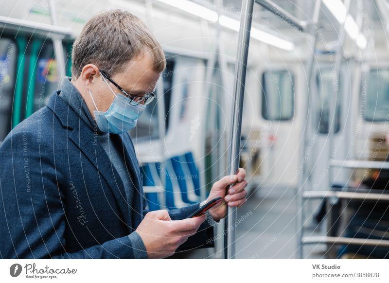 Ein seriöser Mann, der zur Arbeit in die U-Bahn pendelt, trägt eine Virenschutzmaske, da er in einer leeren U-Bahn oder Metro immer in Kontakt mit modernen zellularen Posen steht. Konzept der Entfernung. Öffentliche Verkehrsmittel während des Coronavirus