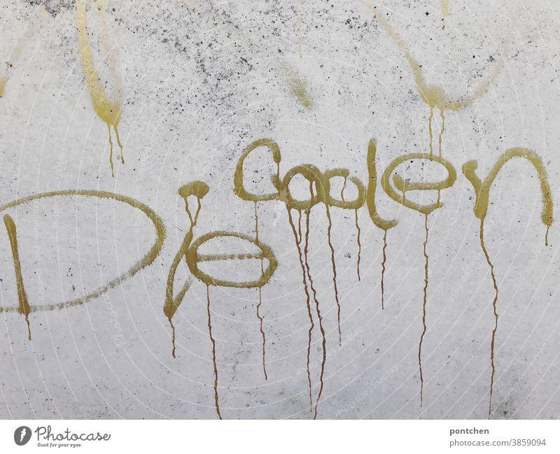 Die coolen steht in goldener Farbe auf einer Wand aus Beton. Graffiti Coolness jugendkultur graffiti Gold schrift wort Schriftzeichen Buchstaben Typographie
