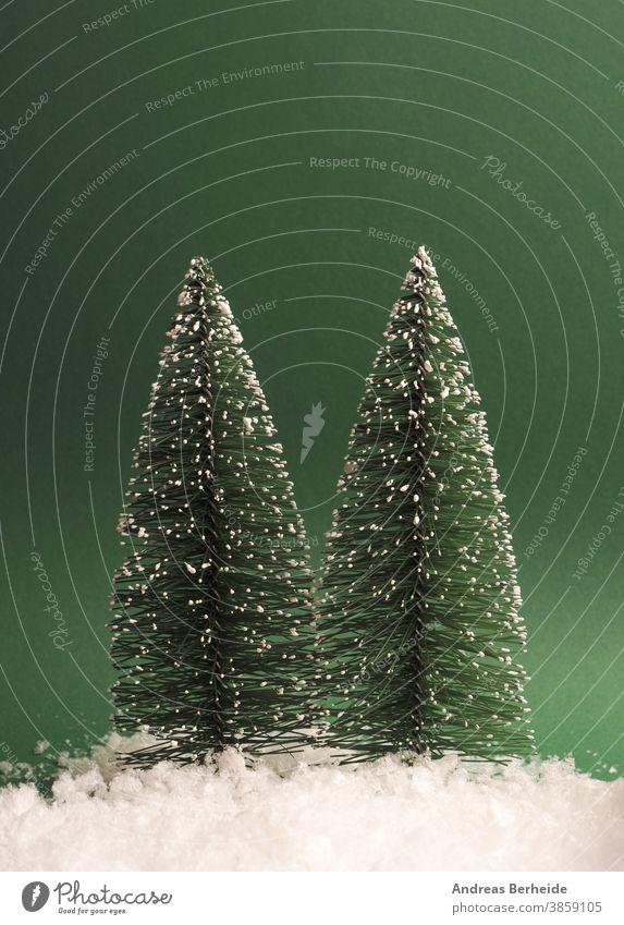 Zwei Tannenbäume mit Schnee auf grünem Papierhintergrund, oben Platz für Text Baum kreativ traditionell Schneeflocke sehr wenige trendy Gruß Textfreiraum