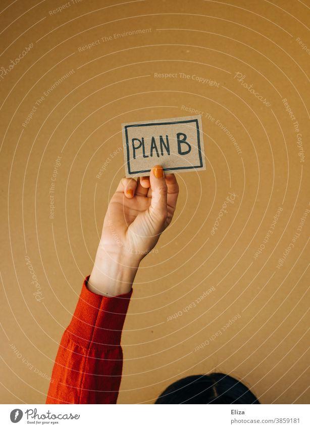 Frau hält ein Schild mit dem Wort Plan B darauf geschrieben Alternative Flexibilität Planung Veränderung alternativ freiberuflich Sicherheit planen
