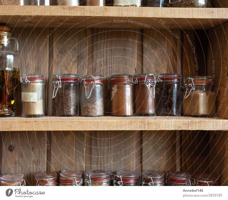 Flaschen mit Gewürzen und Würzmitteln im Holzgestell. Verschiedene verschiedene Bio-Kräuter für den Vintage-Look in der Küche Ablage Lebensmittel Kraut Paprika