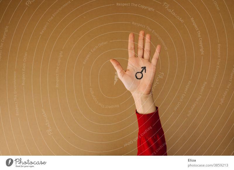 Eine Hand auf dem das Marssymbol für Männlichkeit gemalt ist vor neutralem braunen Hintergrund Mann Symbol maskulin Gendersymbol Mann sein Geschlecht