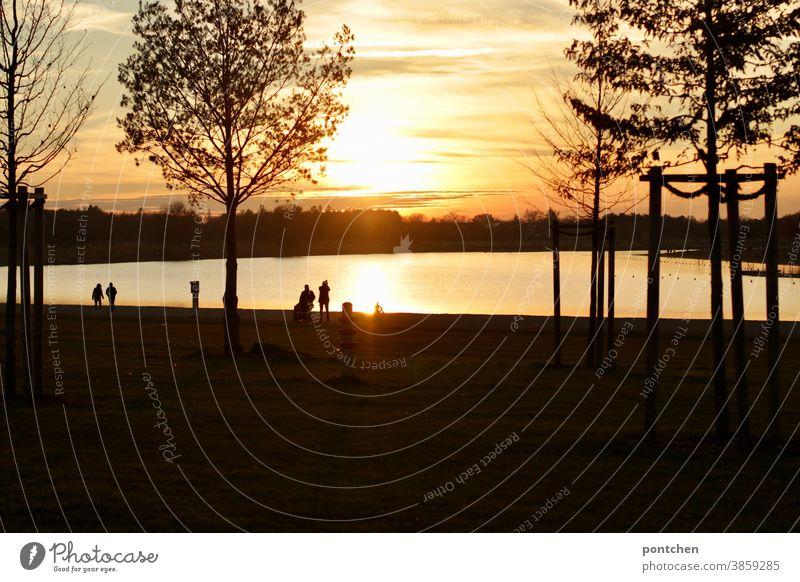 Romantische Stimmung am See bei Sonnenuntergang. Spaziergänger am See. Landschaft see sonne romntisch herbst spaziergänger Wolken Himmel Natur Abend