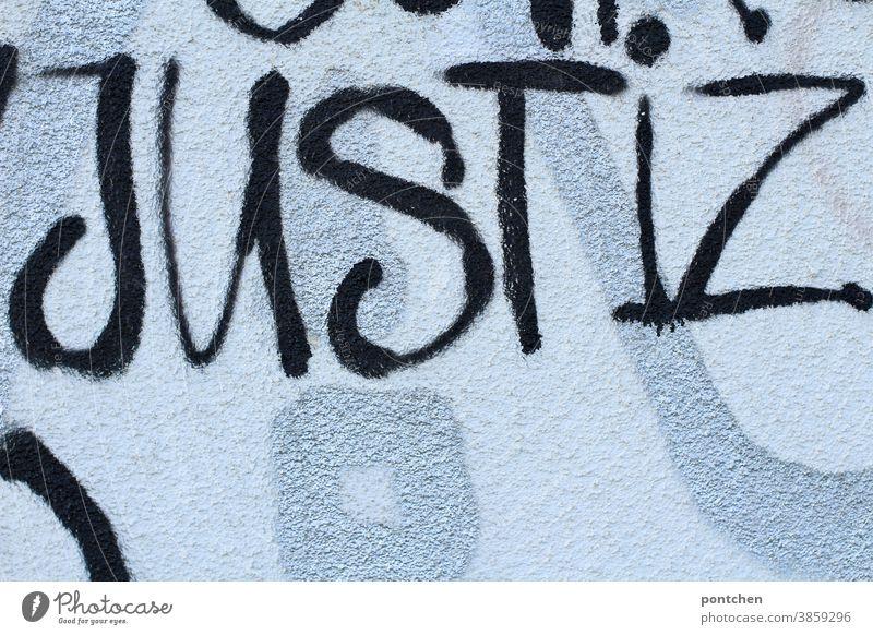 Justiz steht auf einer Mauer. Graffiti in schwarz Justizgewalt Gesetze und Verordnungen Justitia Anwalt Gefängnis Verbrechen Urteil Wort Gericht gesetzt