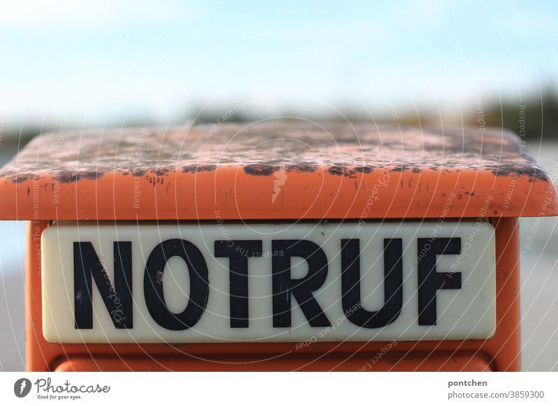 Notruf steht in Großbuchstaben auf einer Notrufsäule in orange notrufsäule gesundheit gefahr drücken alarmieren Notfall Rettung Erste Hilfe Hilfsbereitschaft