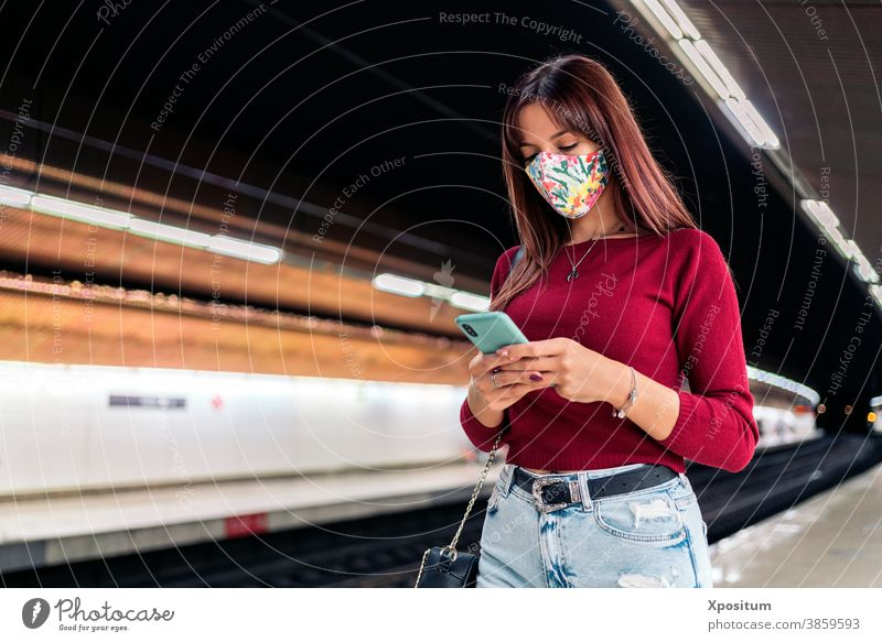 Junge Frau benutzt Smartphone am Bahnhof Porträt Maske Gesicht Mundschutz Lifestyle Podest modern Öffentlich Station Technik & Technologie Verkehr Kaukasier