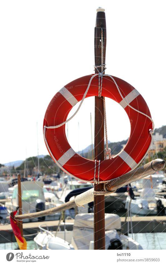 Einsatzbereit - rot weiß neutraler Rettungsring ist an einer Holzstange befestigt Kaimauer Hafen Unglück Hilfe Schutz Sicherheit Erste Hilfe Wasser Bootshafen