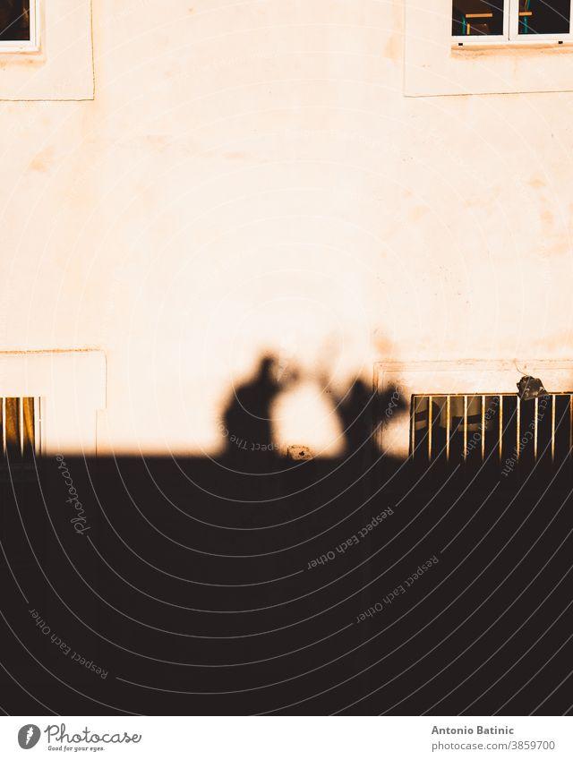 Umrisse, Sihouetten und Schatten werden auf ein Steinhaus geworfen, in dem zwei Menschen zusammen stehen. Eine Person macht das Foto, während die andere die Hände in die Luft hält.
