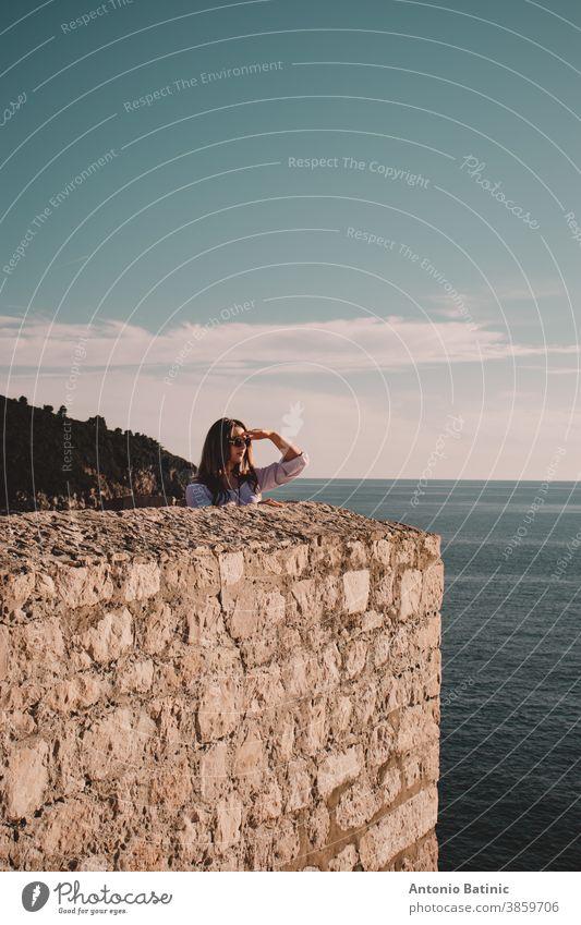 Vertikale Aufnahme einer Brünetten, die auf den Stadtmauern der Stadt Dubrovnik steht, die Hand über die Augen hält und in die Ferne schaut, als ob sie auf der Suche nach etwas ist