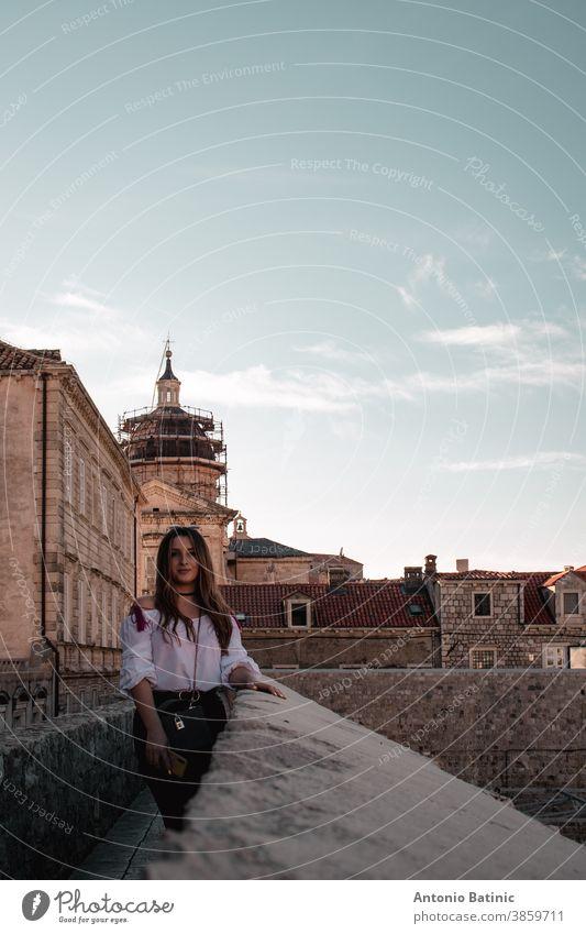 Stimmungsvolles vertikales Porträt einer Brünetten, die an den Mauern der Stadt Dubrovnik steht Urlaub berühmt mittelalterlich Lifestyle Stein Strand