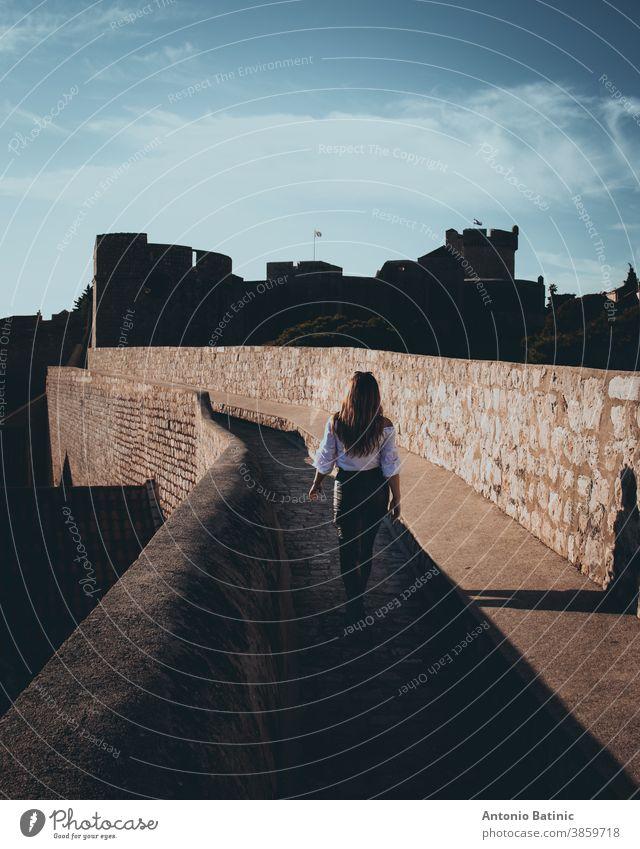 Vertikalaufnahme und Rückansicht eines attraktiven Mädchens, das entlang der Stadtmauer der Stadt Dubrovnik läuft. Dunkler stimmungsvoller Schnitt mit schwarzen und orangefarbenen Highlights