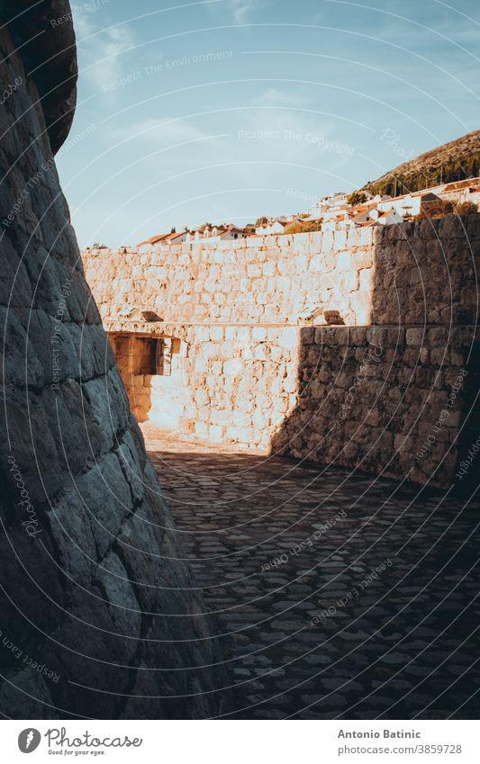 Von Mauern umgebener, schlingenförmiger Kreisbereich um den Turm der Burg Minceta in der Altstadt von Dubrovnik, der von starkem Sonnenlicht beleuchtet wird und mit Schatten Formen bildet