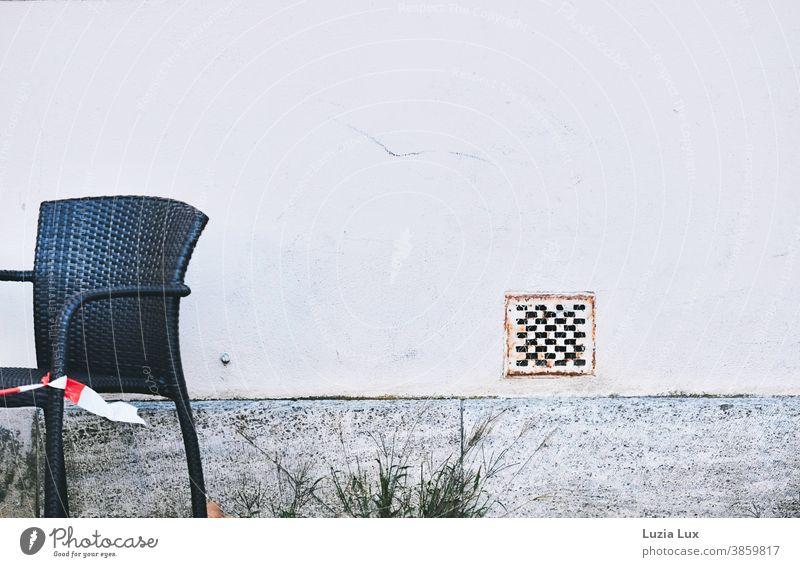 Bitte nicht Platz nehmen: ein Stuhl auf der Terrasse steht leer, Gäste dürfen nicht bewirtet werden Flatterband Absperrung schwarz Wand grau geschlossen