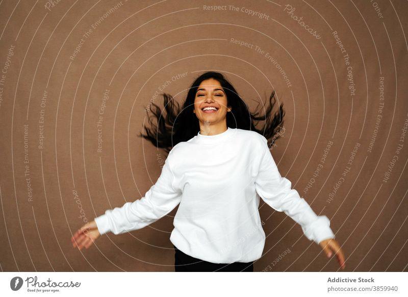 Erfreute Frau mit fliegenden Haaren im Studio fliegendes Haar Spaß haben Lachen Atelier weiß Sweatshirt lässig Stil heiter ethnisch genießen modern positiv