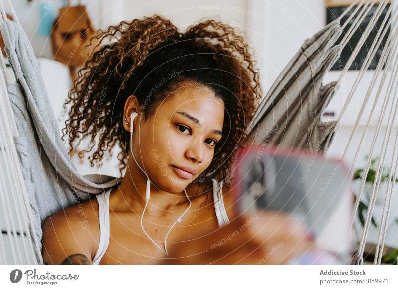Junge schwarze Frau mit Kopfhörern nimmt Selfie zu Hause Kälte zuhören Smartphone ruhen benutzend Hängematte jung Afroamerikaner ethnisch Musik Apparatur Gerät