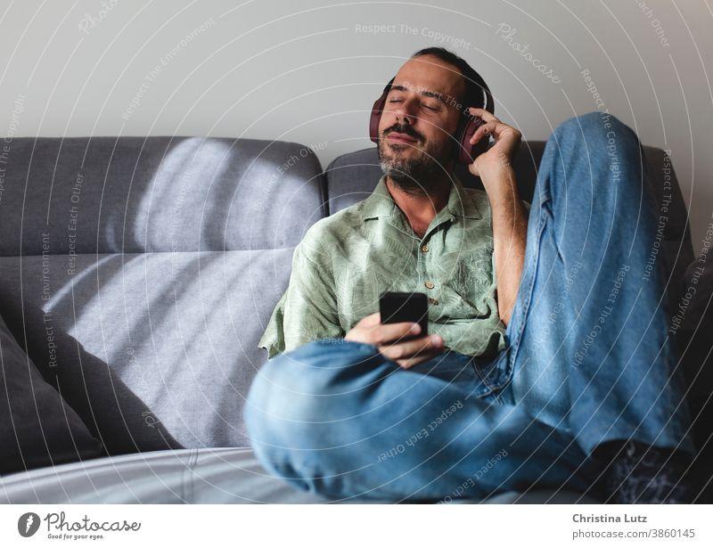 Mann sitzt auf dem Sofa im Wohnzimmer und hört Musik mit Kopfhörern zuhören Sitzen sich[Akk] entspannen Telefon heimwärts Menschen Mobile Person Mitteilung
