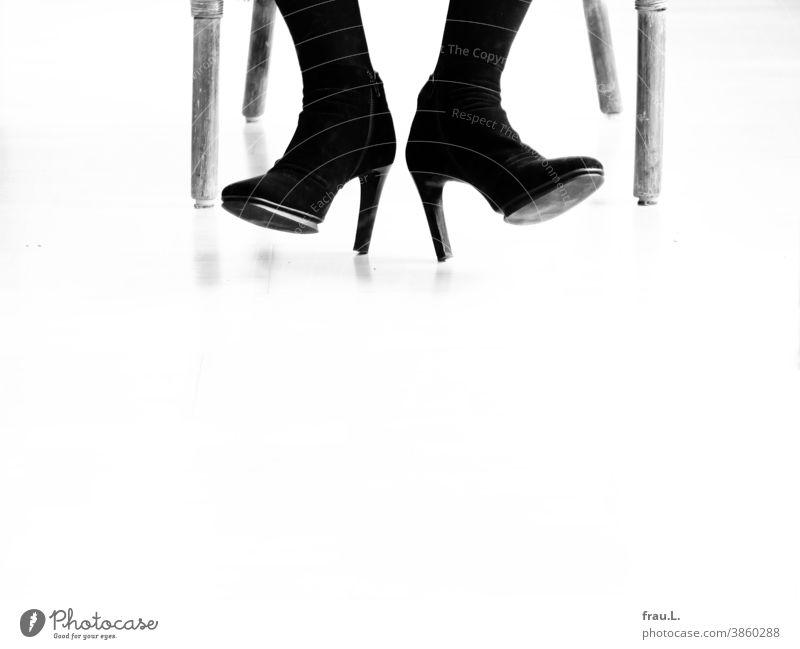 Sechs Beine, zwei Füße, 1 Paar Stiefeletten Frauenbeine sitzen Sessel Schuhe Damenschuhe High Heels Stilettos Korbstuhl
