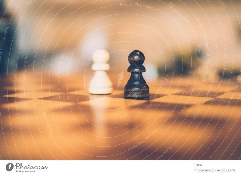 Schwarz gegen weiß - Zwei Bauern auf einem Schachbrett. Schachfiguren schwarz Figuren Rassismus unterschiedlich gegensätzlich Hautfarben Rassengleichheit