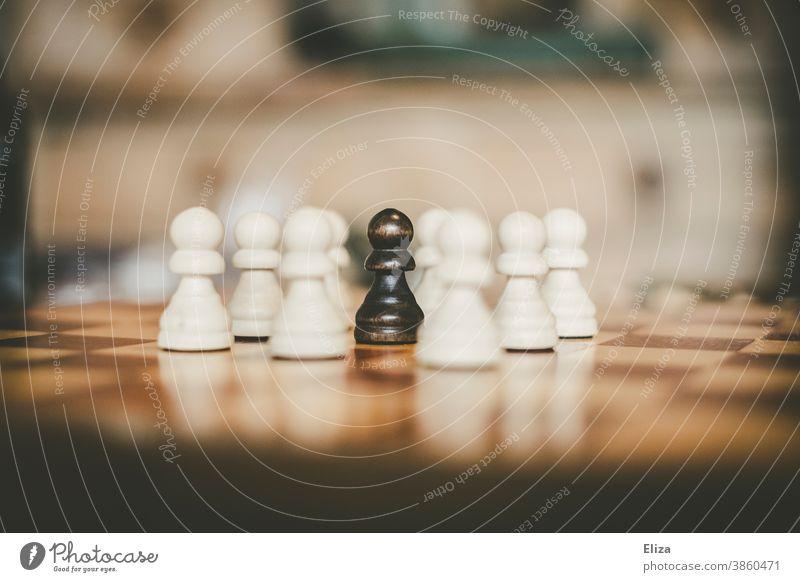 Ein schwarzer Bauer umringt von weißen Bauern auf einem Schachbrett Schachfigur Schachspielen Rassismus umzingelt eingekreist anders Integration Ausländer