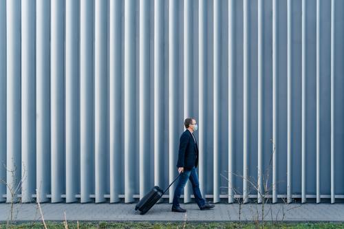 Horizontale Panoramaaufnahme eines Mannes, der im eigenen Land wegen Quarantäne und Pandemie in der Welt eintrifft, geht mit dem Koffer, stellt sich im Freien gegen einen Metallzaun, trägt Gesichtsmaske