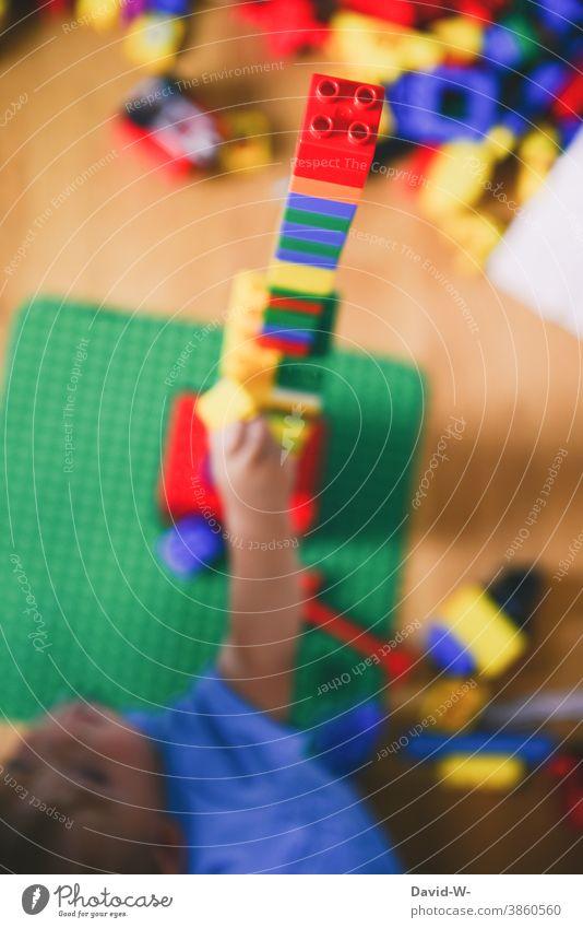 Kind spielt mit Bauklötzen im Kinderzimmer und baut einen Turm Spielzeug spielen Kreativität bauen duplo Spaß Kindheit Freude