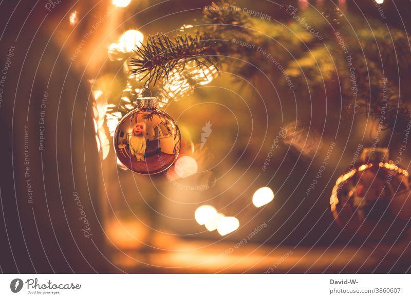 Weihnachten - Kind schaut freudig in eine Christbaumkugel und entdeckt sein Spiegelbild Weihnachten & Advent Weihnachtsbaum spiegeln niedlich Vorfreude wärme