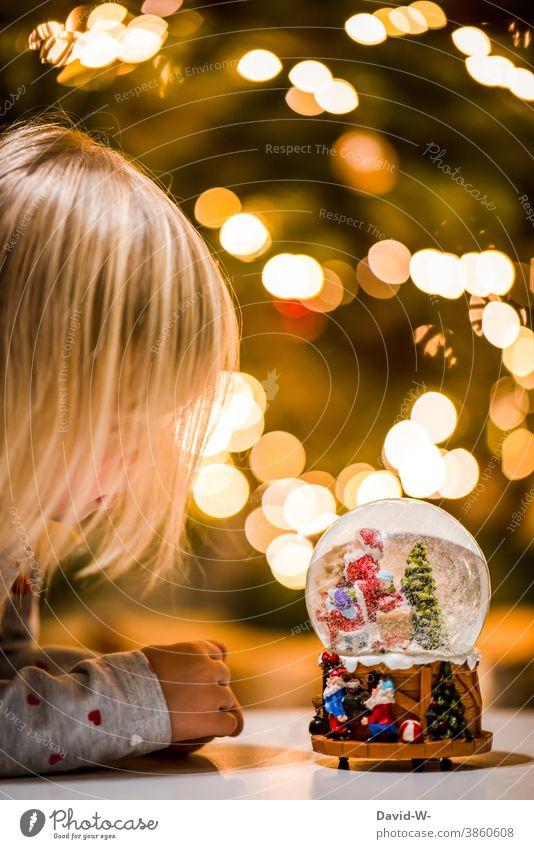 kleines Mädchen schaut an weihnachten in eine Schneekugel Weihnachten & Advent wünschen Wunsch Glaube Vorfreude Weihnachtsmann leuchten Weihnachtsbaum Freude