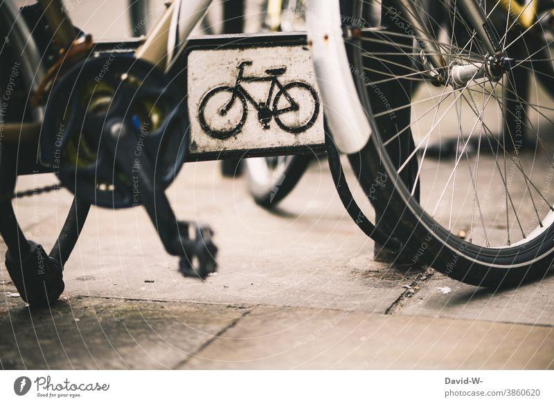 abgeschlossenes Fahrrad und ein Schild auf dem ein Rad abgebildet ist Schloss stehen parken Stadt Verkehrsmittel Zeichen