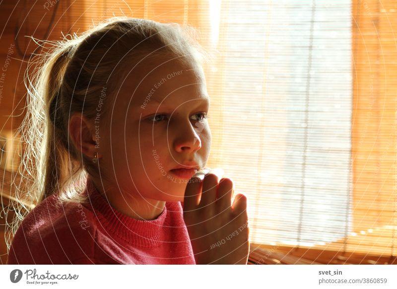 Ein blondes Teenagermädchen sitzt bei Tageslicht durch einen Vorhang an einem Fenster und schaut nachdenklich nach vorne, die Hand ans Kinn. Porträt eines nachdenklichen blonden Mädchens.