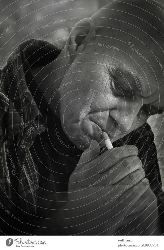 Porträt eines Rauchers Mann rauchen Zigarette anzünden Gesicht Sucht Genuss Entspannung Gewohnheit Abhängigkeit Nikotin Gesundheitsrisiko Suchtverhalten