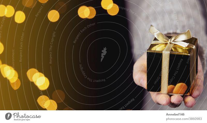Hand hält eine goldene Geschenkverpackung mit Goldband, Bokeh-Glitzer-Hintergrund, Weihnachts- oder Geburtstagsgeschenkkonzept mit Platz für Text Feiertag