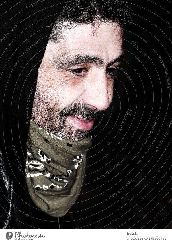 Ein lächelnder Mann sitzen gutaussehend attraktiv Porträt Halstuch Bart Kapuze Atemschutz Coronavirus SARS-CoV-2