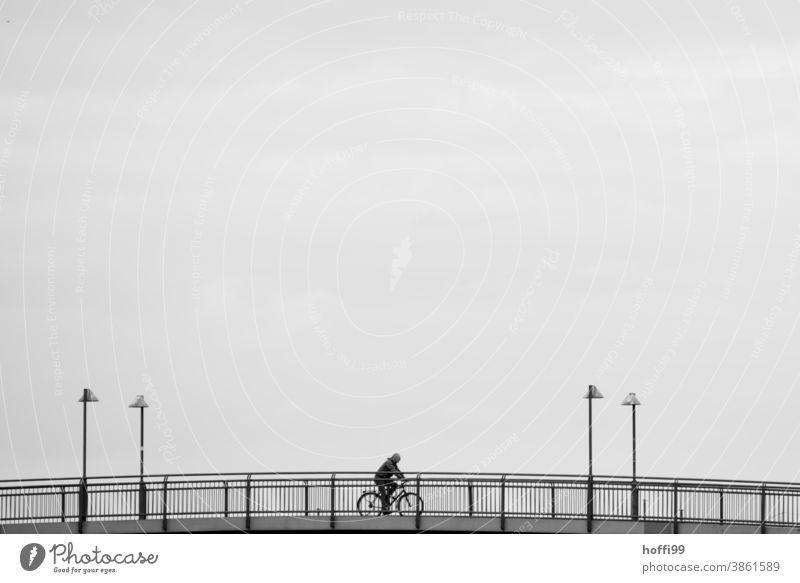 Fahrrad fahren auf einer Brücke - die Laternen rahmen das Geschehen kunstvoll ein Fahrradfahren Mensch Minimalismus Lifestyle Erwachsene Silhouette Bewegung