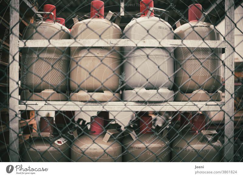 Gasflaschen ordentlich im Regal eingelagert Propan Propangas Technik & Technologie Brennstoff rot grau Energie Lager Tank Kraft Gasflamme Textfreiraum oben