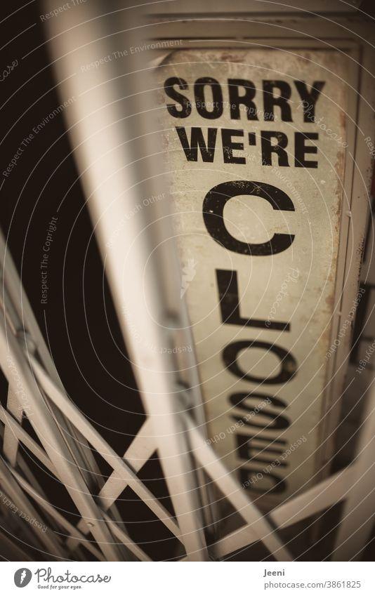 Ein Schild eines Geschäfts hinter einer verschlossenen Gittertür - schwarze Aufschrift auf hellem Untergrund: sorry we're closed I Entschuldigung, es ist geschlossen I corona thoughts