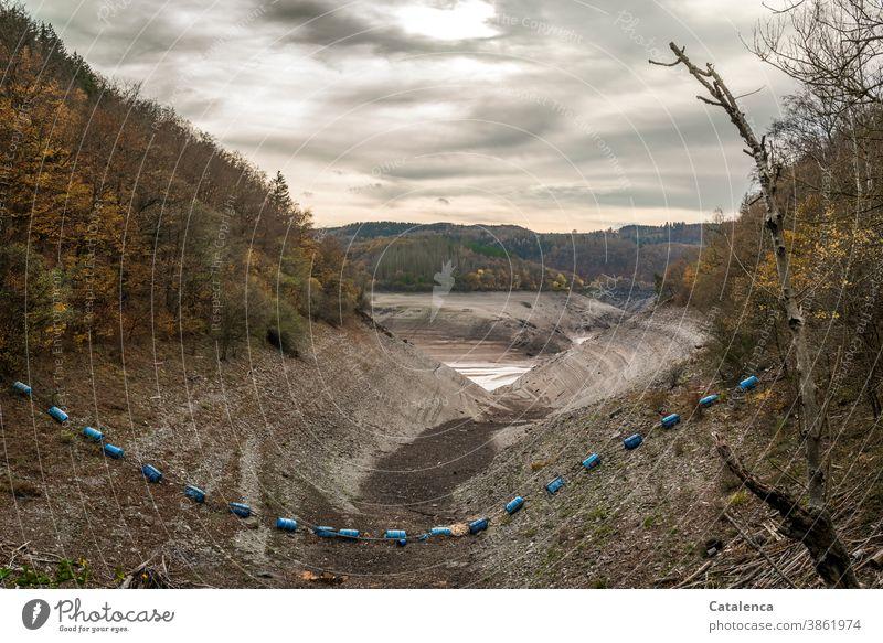 Die Begrenzung aus blauen Plastiktonnen in dem entleerten Stausee im Herbst erreicht ihren Tiefpunkt Grau Wolken Himmel herbstlich Steine Lehm Urft Fluß