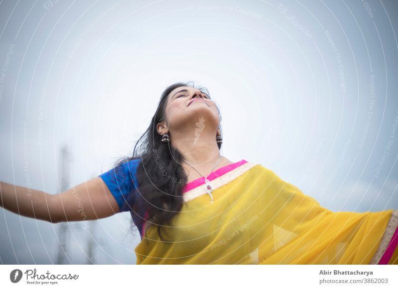 Eine junge und schöne indisch-bengalische brünette Frau in traditionellem gelben Sari und blauer Bluse steht, während sie ihre Arme auf dem Dach unter blauem Himmel mit Wolken ausbreitet. Indischer Lebensstil