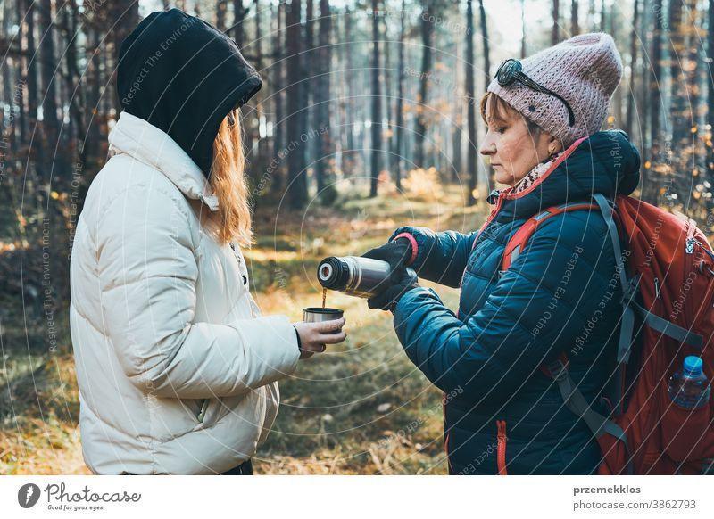 Mutter und Tochter mit Rucksack haben Pause während der Herbstreise an einem kalten Herbsttag aktiv Aktivität Abenteuer Backpacker Kaffee Tasse Ausflugsziel