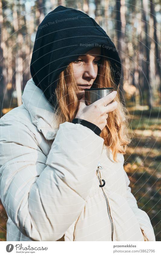 Frau mit Kapuze, die während einer Herbstreise Pause macht und am kalten Herbsttag eine Tasse mit heißem Getränk aus der Thermoskanne hält aktiv Aktivität
