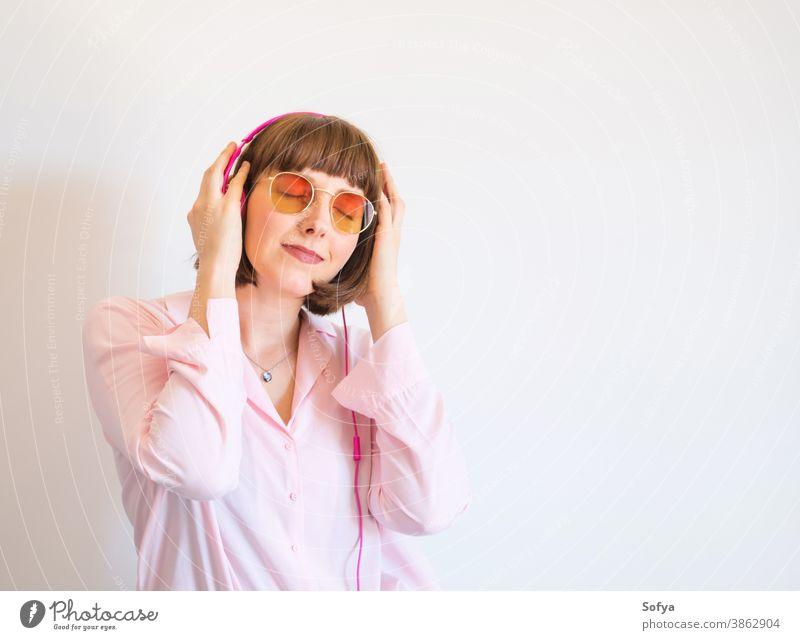 Junge glückliche Frau in rosa Hemd mit Kopfhörern Mode Sonnenbrille Lächeln Musik zuhören vertieft engagiert Telefon Glück jung Farbe Lifestyle benutzend