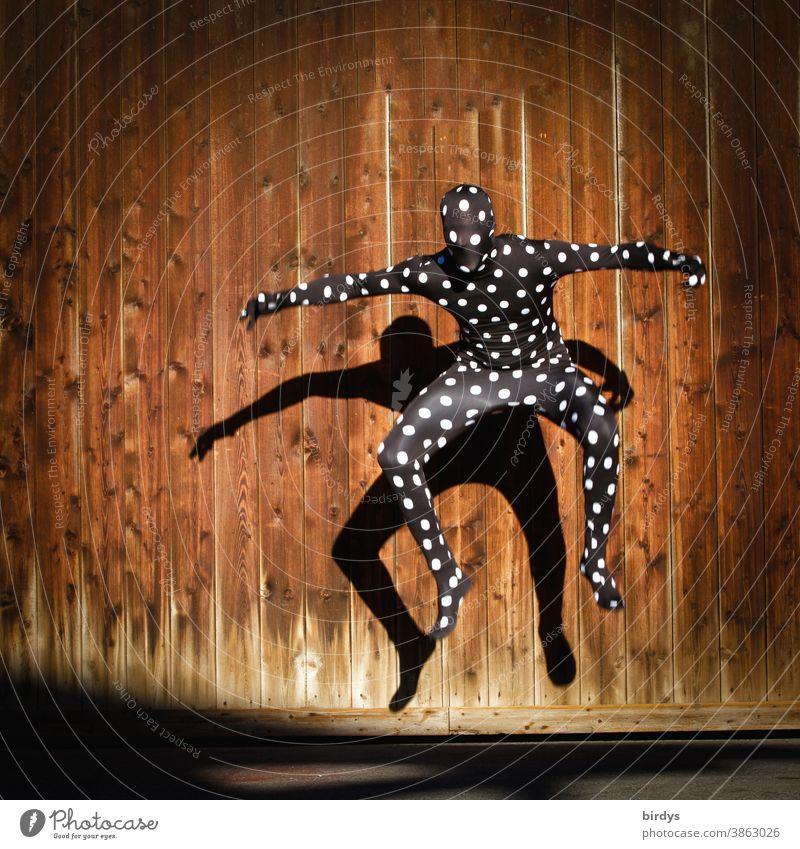 Menschliche Gestalt im gepunktetem Morphsuitkostüm , Sprung in die Luft mit Schattenwurf auf eine Holzwand Morphsuite ganzkörperanzug Punkte im Sprung androgyn