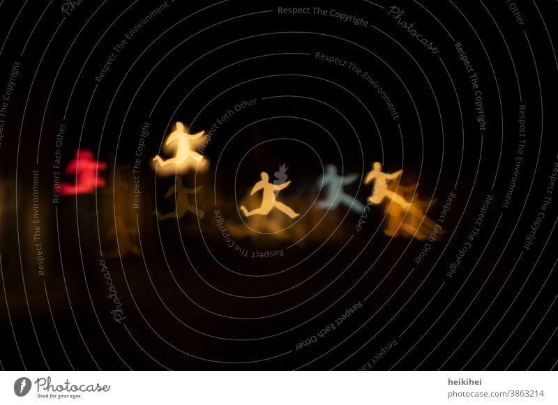 Tanzende Licht-Männchen Lichterscheinung Mensch hüpfen rennen laufen springen Freude Bewegung Begeisterung Bokeh Effekt gelb rot blau orange schwarz Nacht