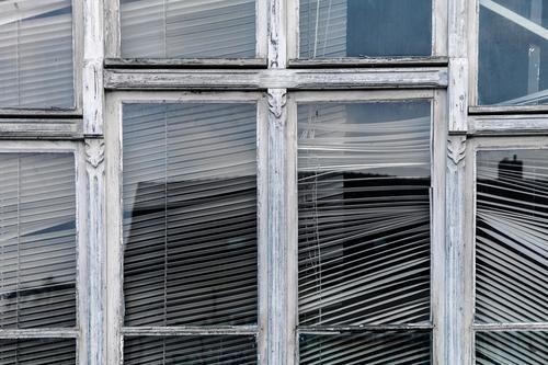 Hinter diesem Fenster rührt sich schon lange nichts mehr Fensterrahmen verwittert alt verziert Jalousie schräg kaputt Glas Spiegelung verlassen lost place