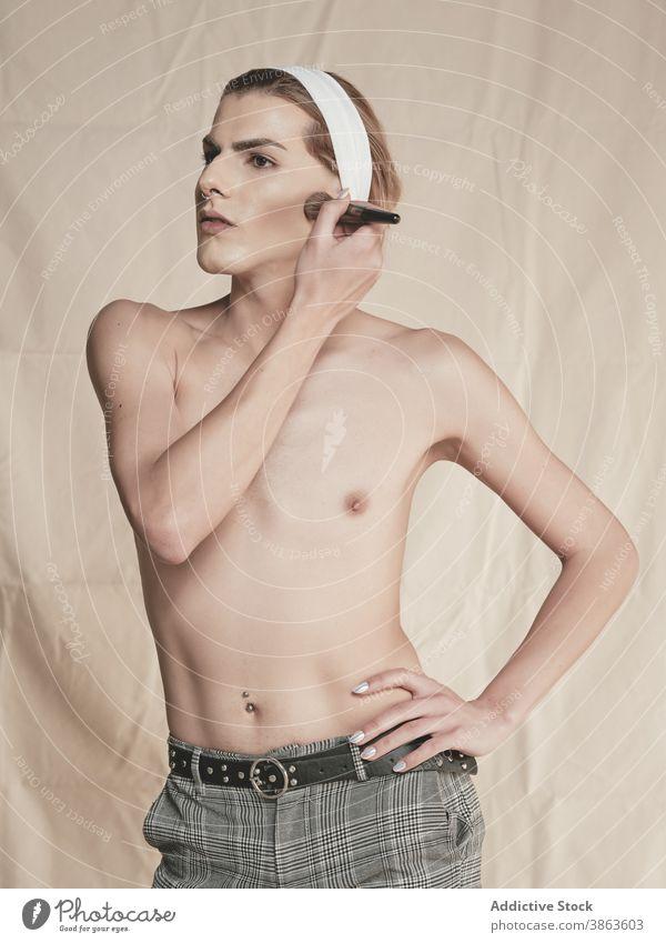 Stilvolle shirtless Kerl Anwendung Make-up Mann androgyn bewerben Vorschein Rouge schlank Hand auf der Taille Transgender männlich jung Model ohne Hemd Wange