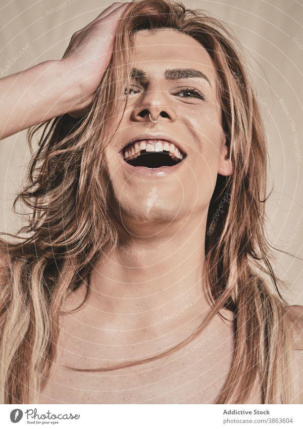 Junger hemdloser androgyner Mann lachend Lachen Make-up ohne Hemd Vorschein Transgender Glück Model jung männlich Stirnband Piercing aufgeregt queer lgbtq