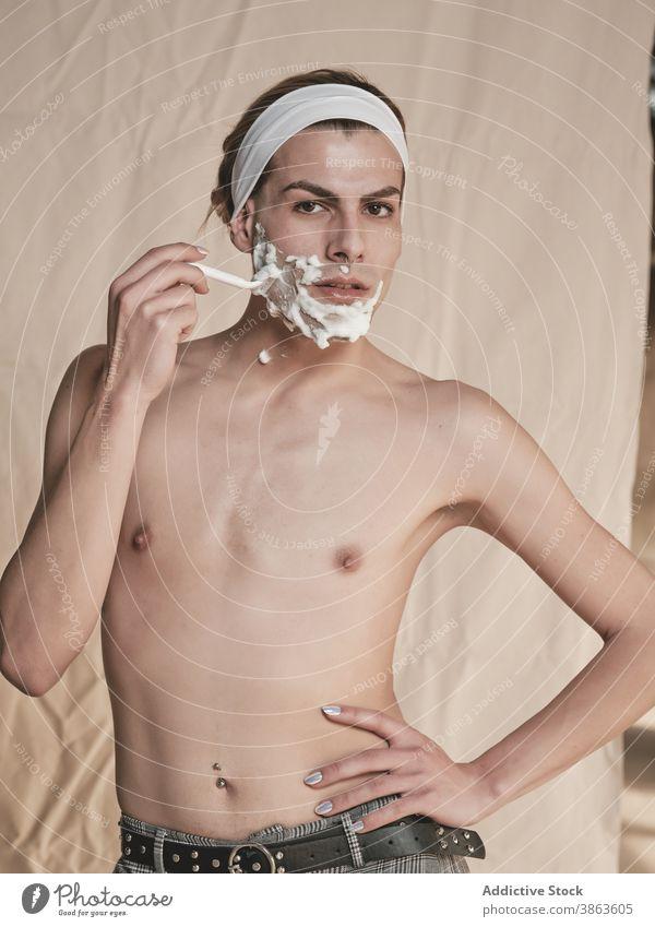 Androgyner junger Mann rasiert Gesicht Rasieren androgyn Transgender Hygiene Pflege vorbereiten Rasierer ohne Hemd schlank männlich Maniküre schäumen Hautpflege
