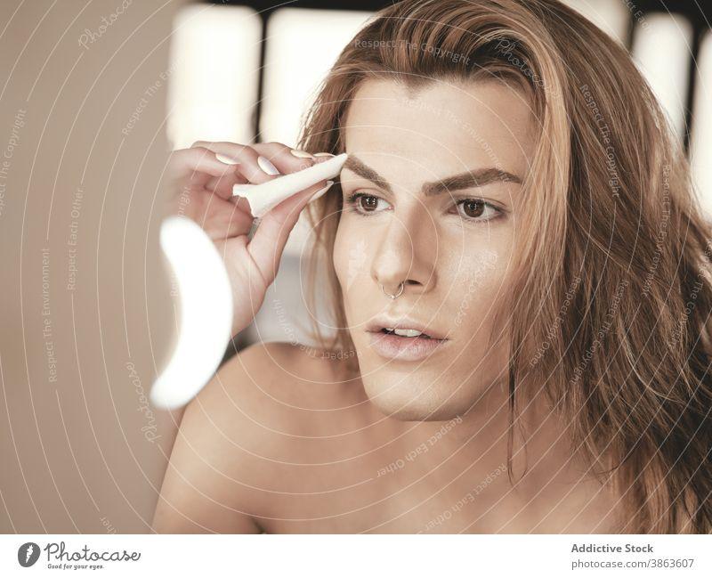 Androgyner Mann mit langen Haaren beim Auftragen von Make-up bewerben Atelier androgyn Schönheit Fundament Spiegel Transgender Vorschein männlich jung Model