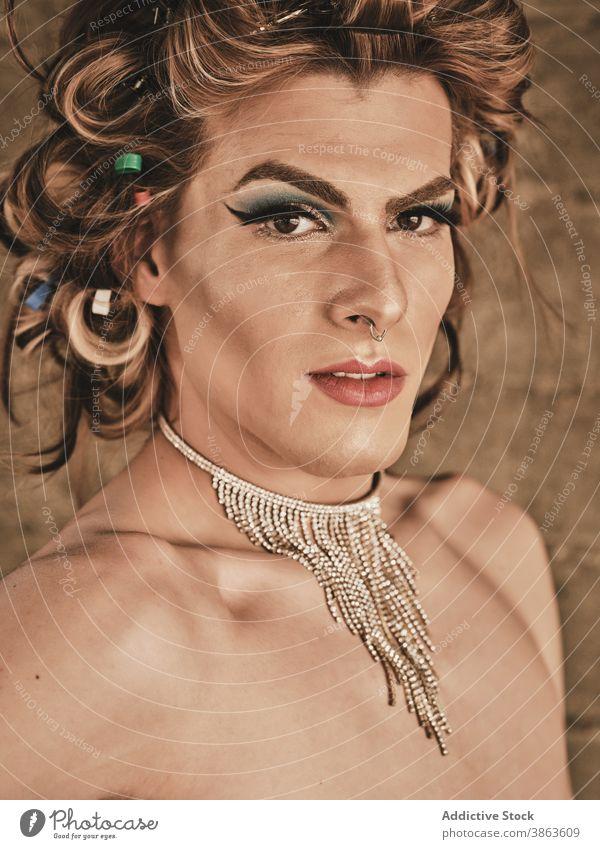 Dragqueen mit Halskette schaut in die Kamera Mann Transgender Make-up elegant Vorschein androgyn Frisur Reichtum Porträt ohne Hemd männlich jung Model Glamour